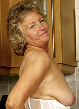 Granny housewife posing nude in the kitchen